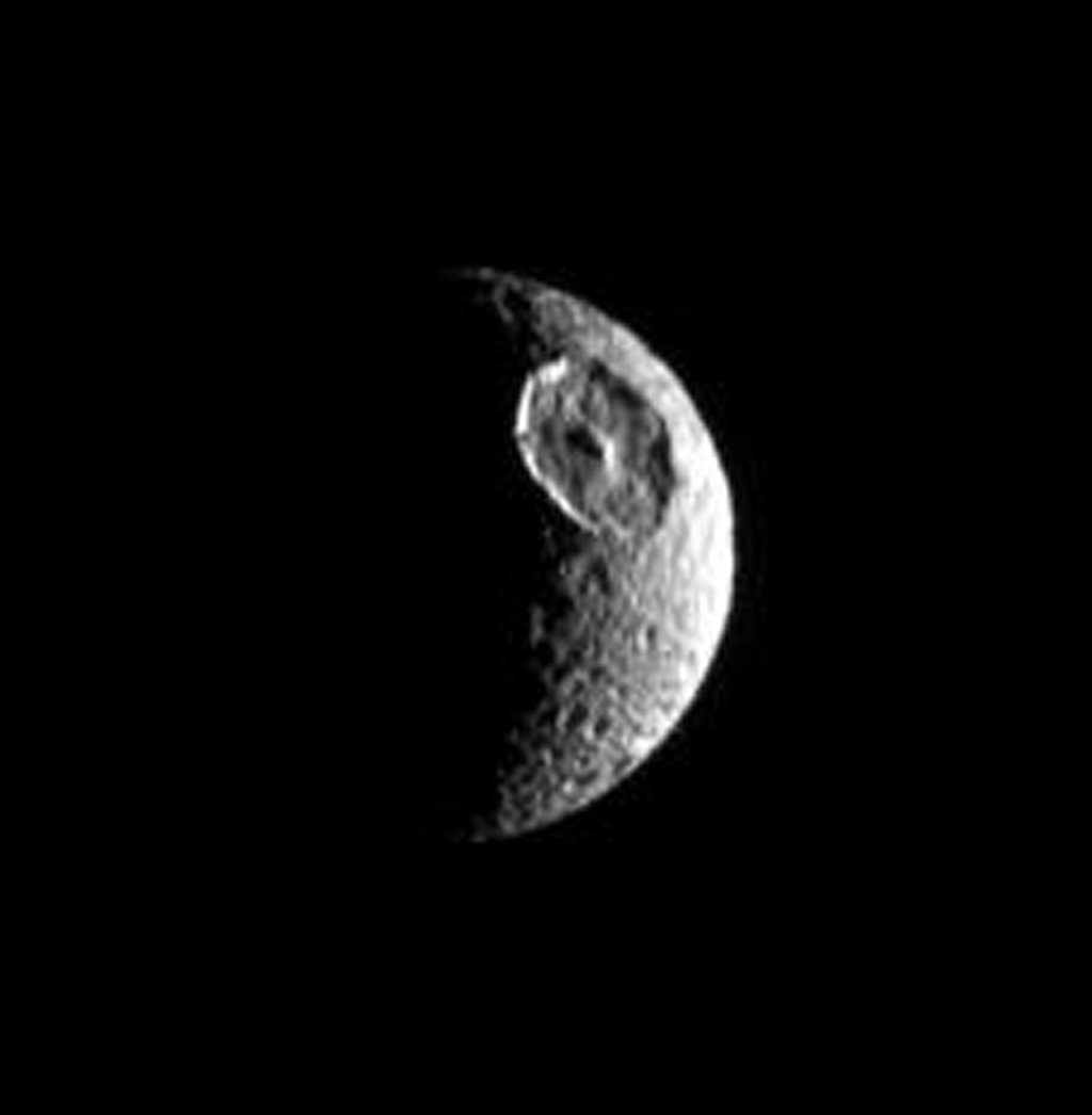 The great basin that interrupts the contours of this moon's crescent identifies the satellite unmistakably as Mimas. The giant crater Herschel is this moon's most obvious feature as seen by NASA's Cassini spacecraft.