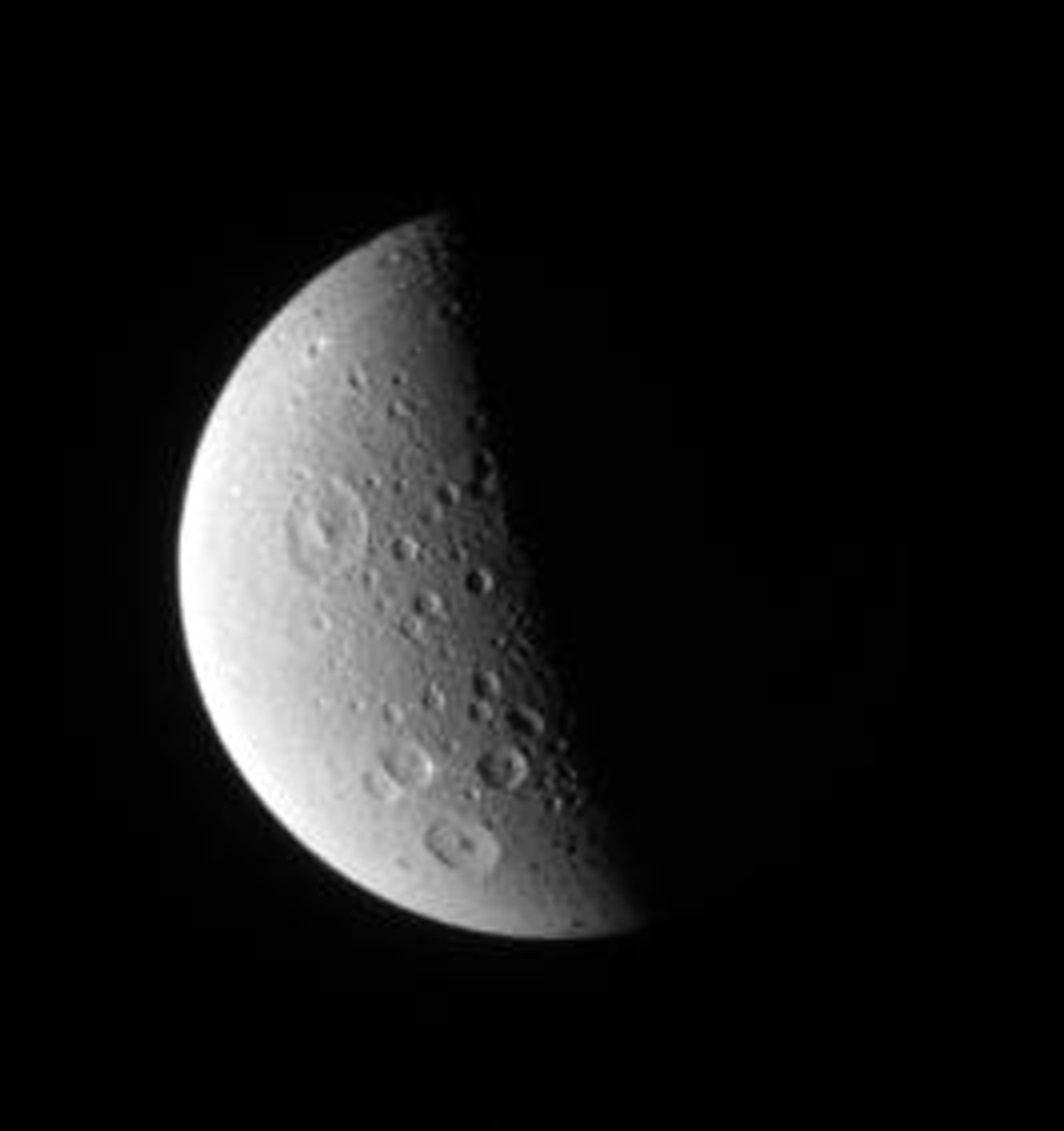 Craters of all sizes litter the landscape on Saturn's Dione. The larger craters in this view display prominent central peak in this image captured by NASA's Cassini spacecraft on Oct. 12, 2006.