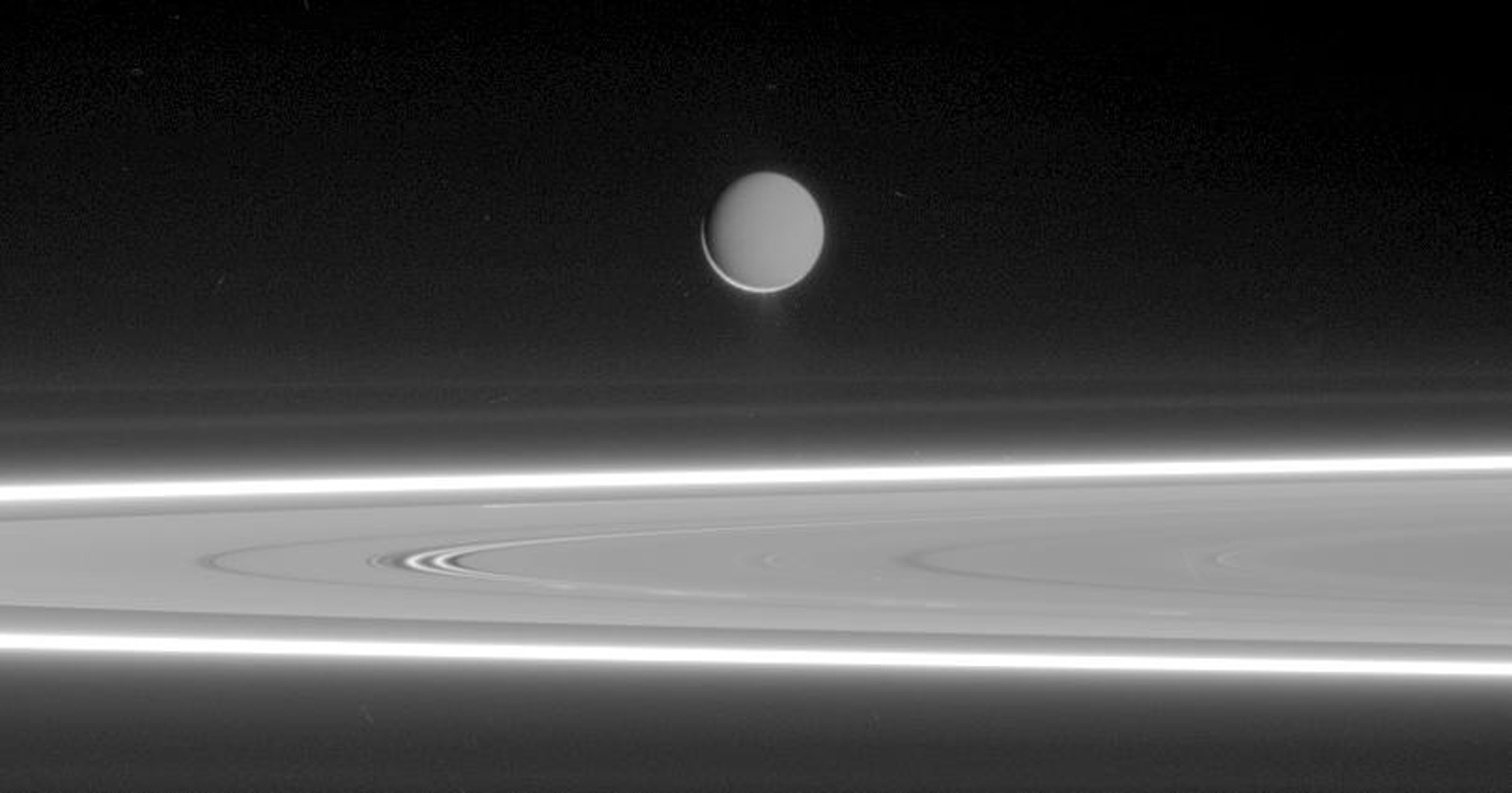 Lit by reflected light from Saturn, Enceladus appears to hover above the gleaming rings, its well-defined ice particle jets spraying a continuous hail of tiny ice grains as seen by NASA's Cassini spacecraft.