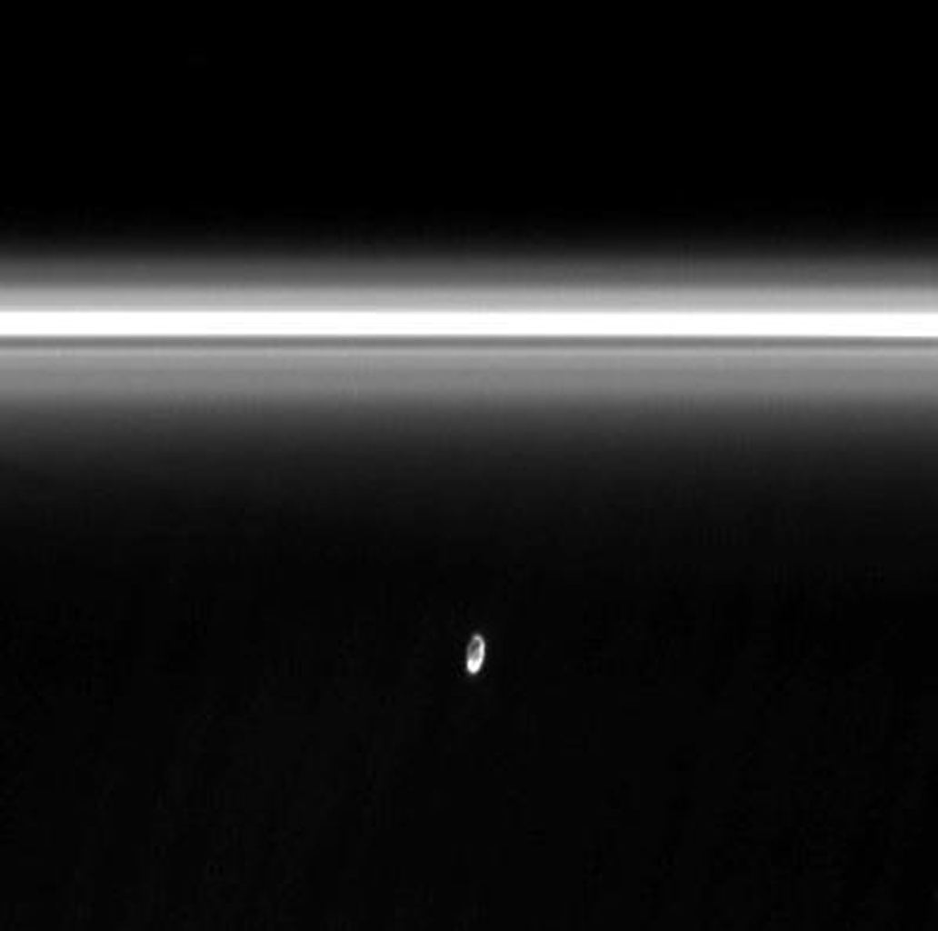 The moon Prometheus slowly collides with the diffuse inner edge of Saturn's F ring in image from NASA's Cassini spacecraft. The oblong moon pulls a streamer of material from the ring and leaves behind a dark channel.
