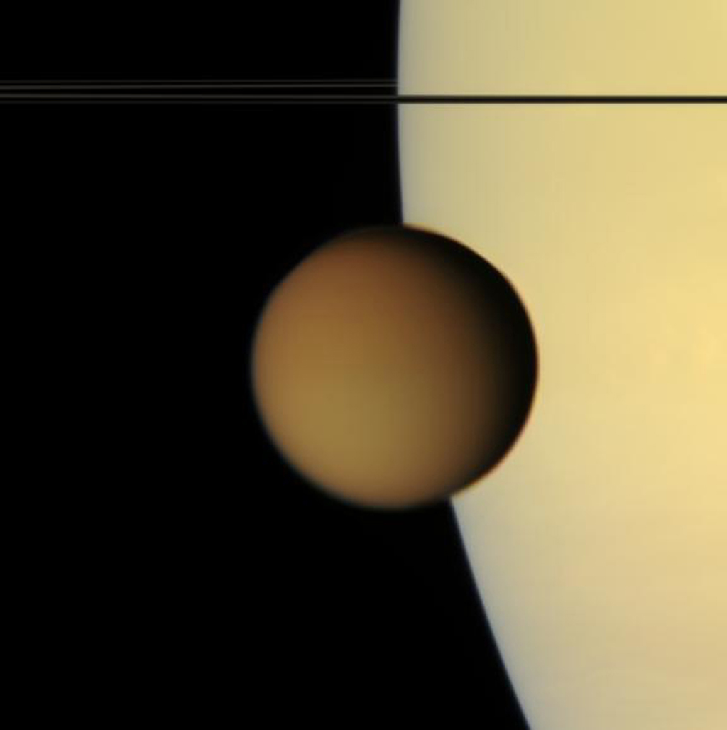 The murky orange disk of Saturn's moon Titan glides past -- a silent, floating sphere transiting Saturn. Titan is 5,150 kilometers (3200 miles) across. This view from NASA's Cassini spacecraft was acquired from less than a degree above Saturn's ringplane.