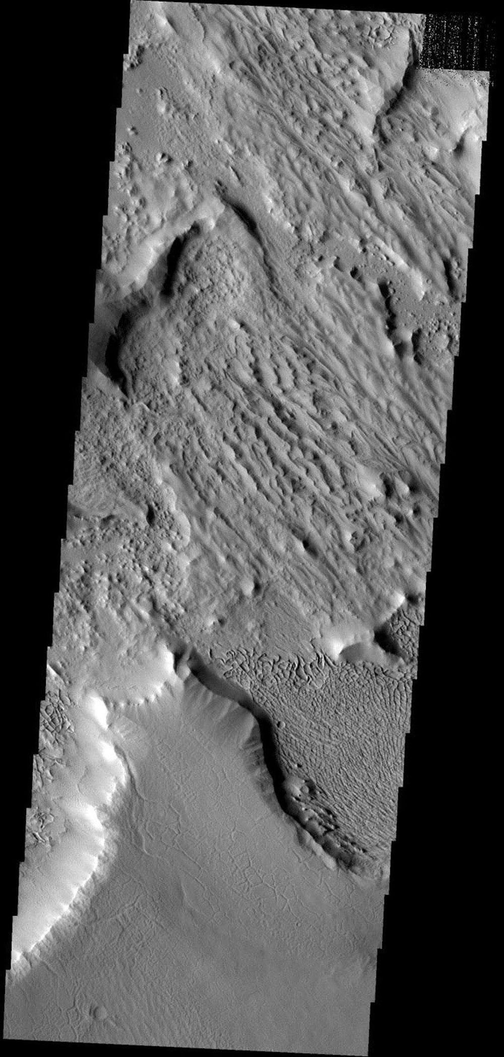 This image has a cracked plateau of material next to a low region of interconnected small ridges. This region is located at the northwestern end of Gordii Dorsum on Mars as seen by NASA's 2001 Mars Odyssey spacecraft.