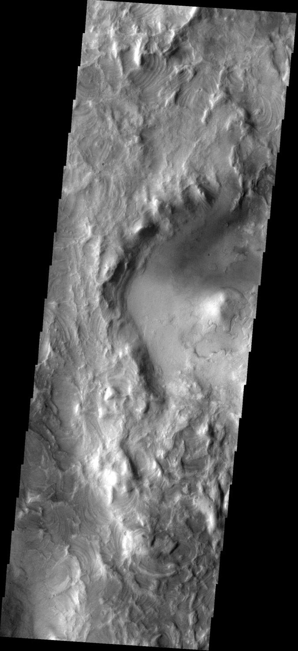 The erosion of the western rim of Hellas Basin on Mars has exposed a surface composed of layered material as seen by NASA's 2001 Mars Odyssey.