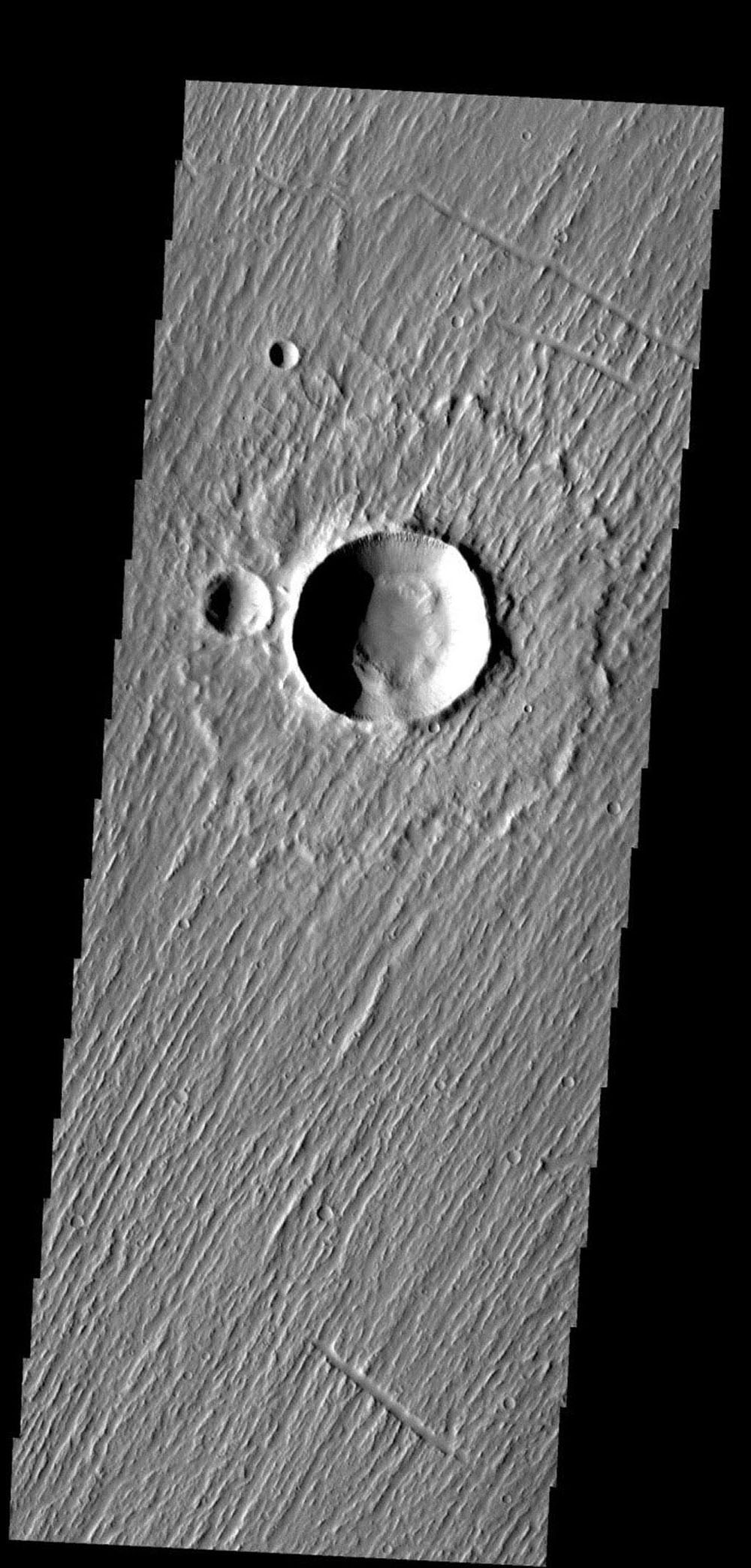 This image is from NASA's 2001 Mars Odyssey. Linear ridges on Mars cover this entire image - except for the interior of the craters.