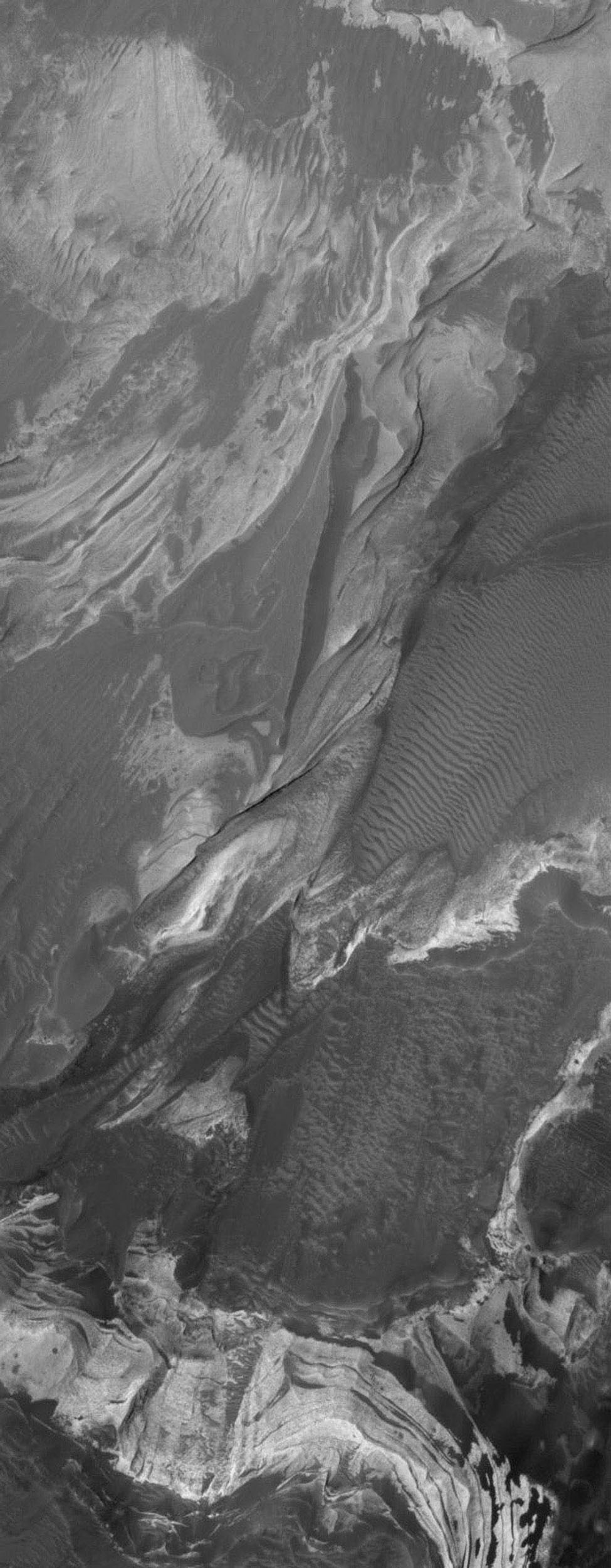NASA's Mars Global Surveyor shows layered, light-toned, sedimentary rocks that have been exposed by erosion in Coprates Chasma, one of the many chasms which comprise the Valles Marineris trough system on Mars.