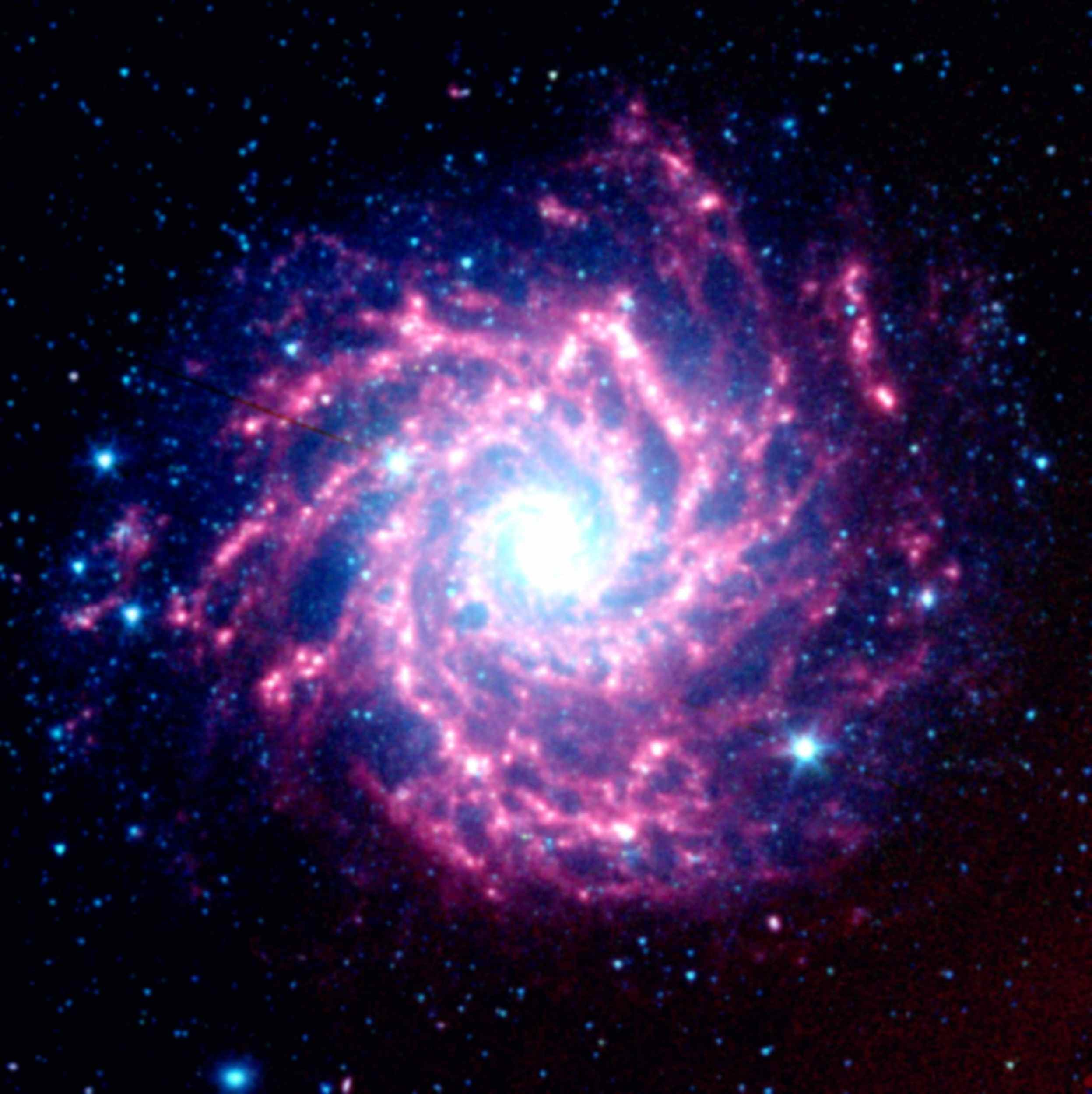 Astronomers using NASA's Spitzer Space Telescope have spotted a 'dust factory' 30 million light-years away in the spiral galaxy M74. The factory is located at the scene of a massive star's explosive death, or supernova.