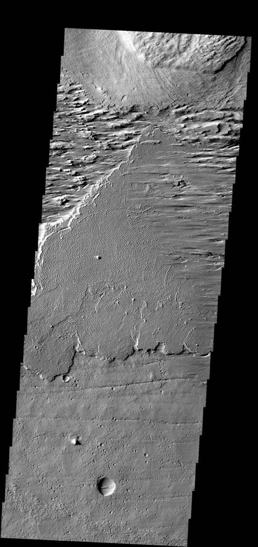 This image shows a region near Olympus Mons on Mars where wind has been moving loose material across the lava flows in the center of the image from NASA's 2001 Mars Odyssey.