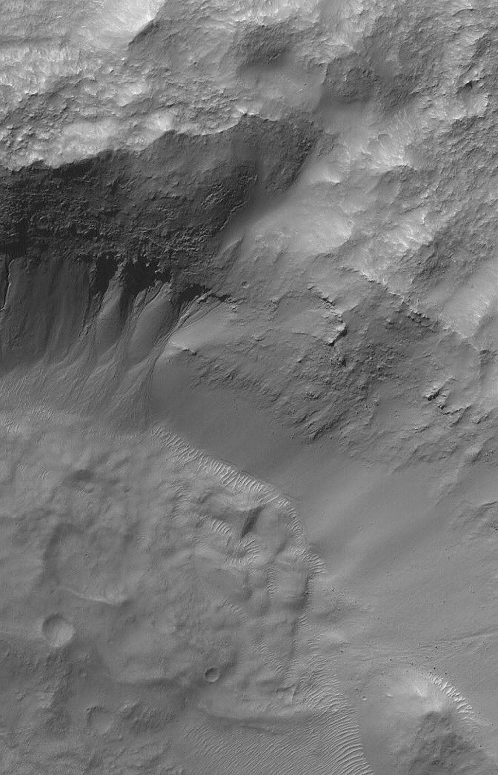 This image from NASA's Mars Global Surveyor shows gullies on the wall of a martian south mid-latitude impact crater. The channels in each gully head beneath an eroding overhang of layered rock.