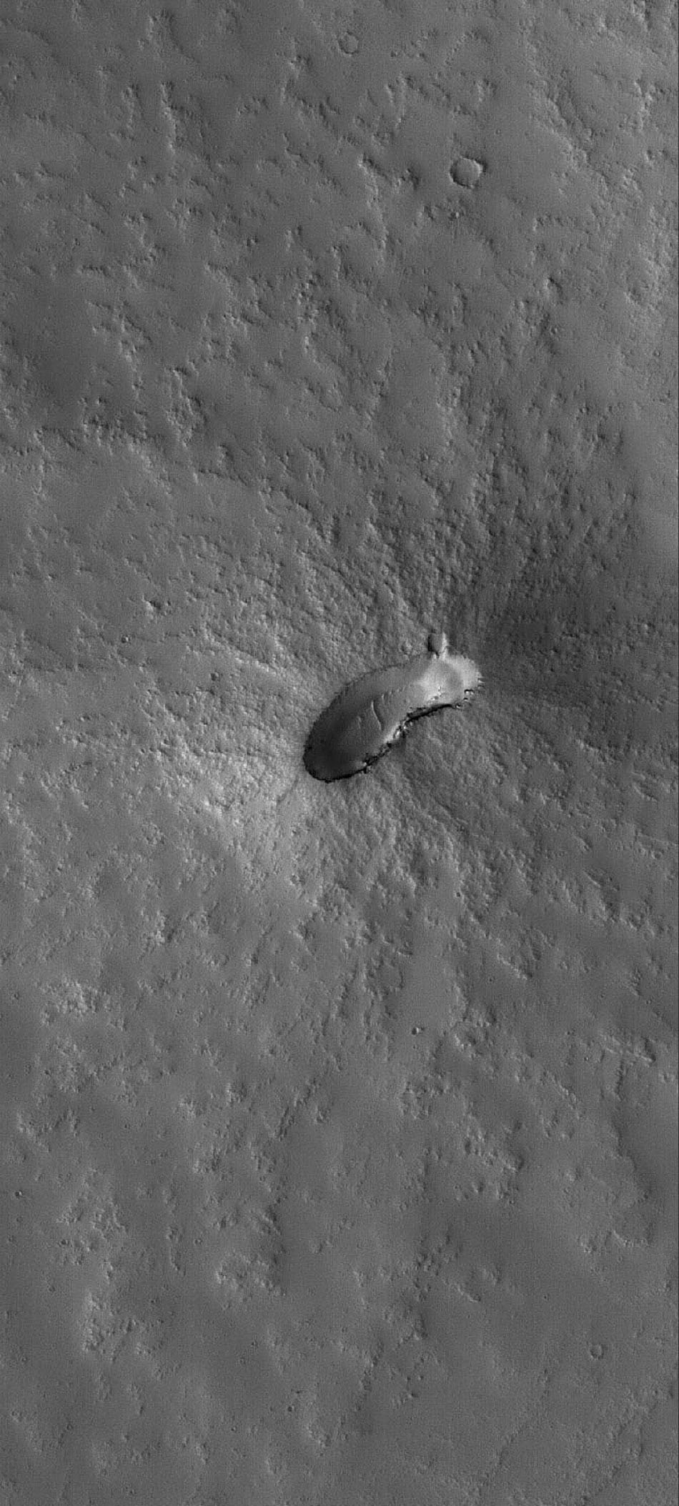 This image from NASA's Mars Global Surveyor shows a small, dust-mantled volcano on the plains east of the giant martian volcano, Pavonis Mons.