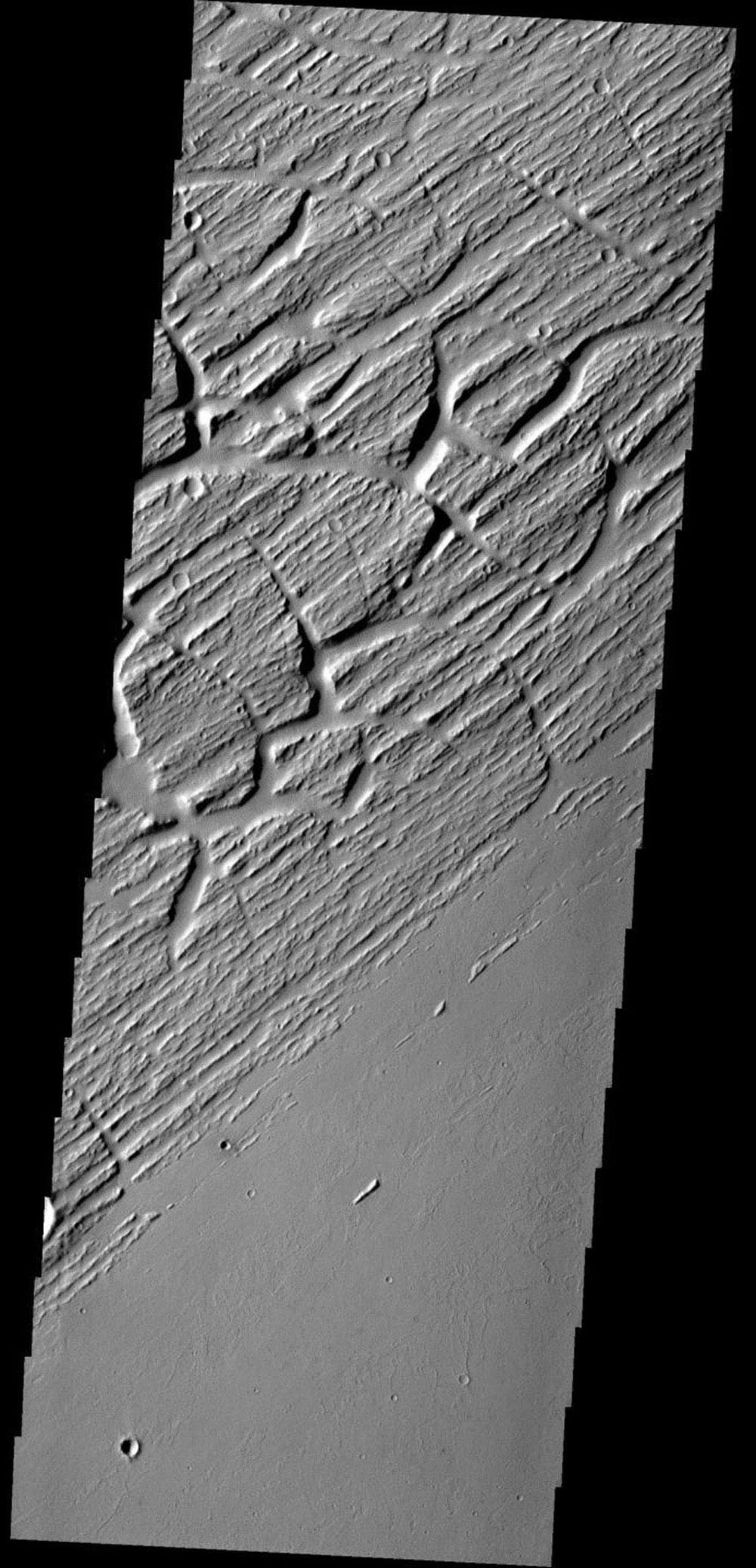 This image shows part of Sacra Sulci, a region of high standing grooves, crosscut by cracks and fractures. Lava flows are present to the south and sand dunes fill the floor of the large cracks on Mars as seen by NASA's Mars Odyssey spacecraft.