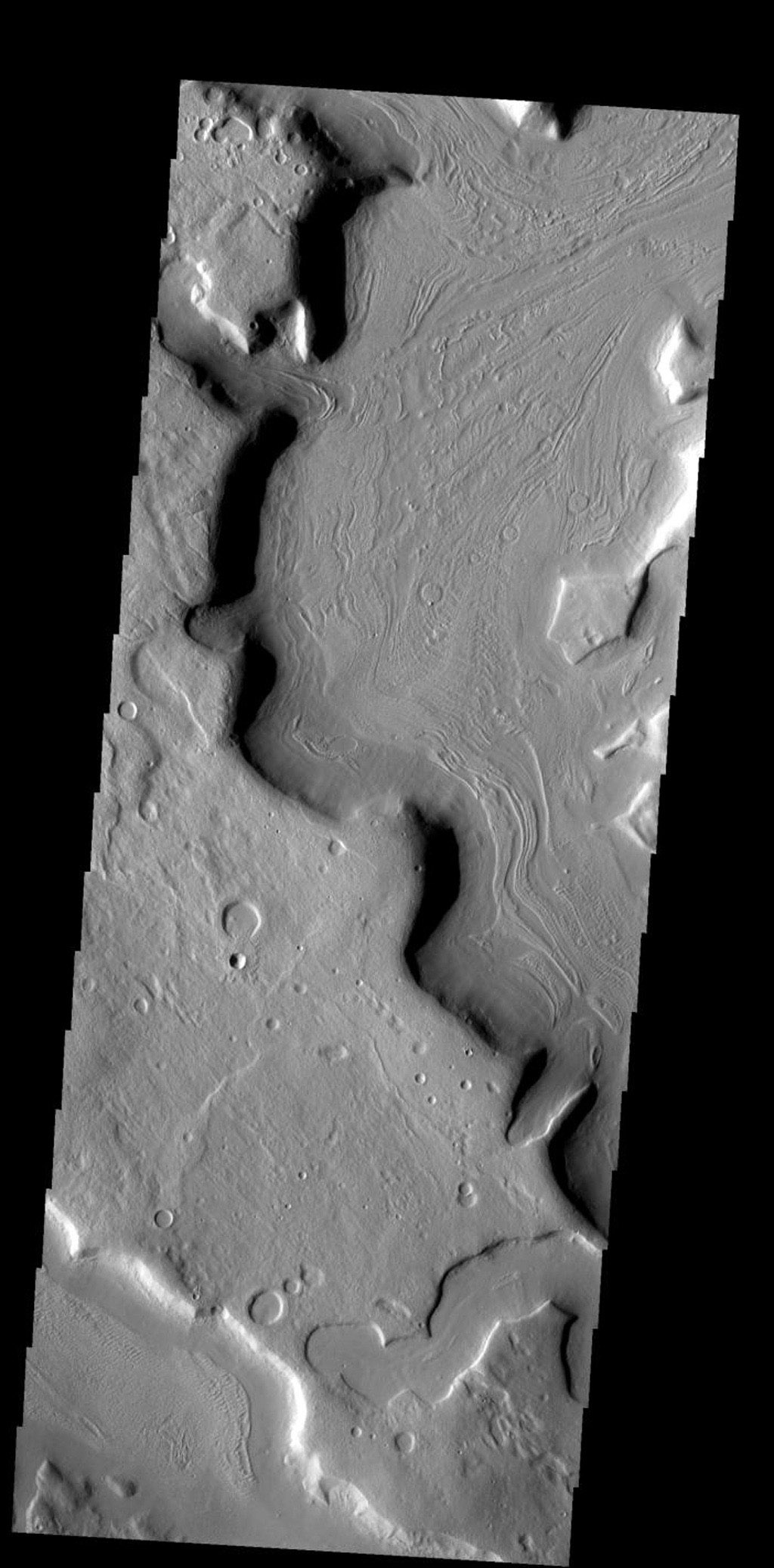The odd pattern on the floor of this channel suggests that a volitile such as ice played a part in its formation on Mars as seen by NASA's Mars Odyssey spacecraft.
