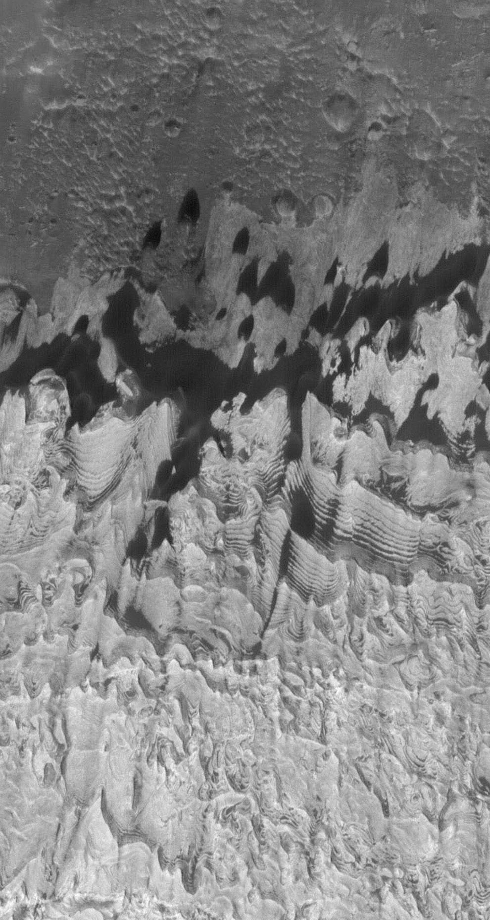 NASA's Mars Global Surveyor shows cracks layered, light-toned outcrops of sedimentary rock in Becquerel Crater. The outcrops are juxtaposed against a dark-toned substrate which occupies the upper (northern) portion of the image.