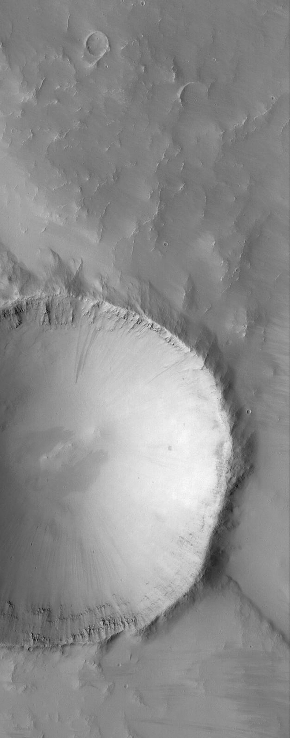 This image from NASA's Mars Global Surveyor shows an impact crater that is approximately 3.5 kilometers (2.2 miles) in diameter. Layered rock units are visible on the inside of the raised crater rim.