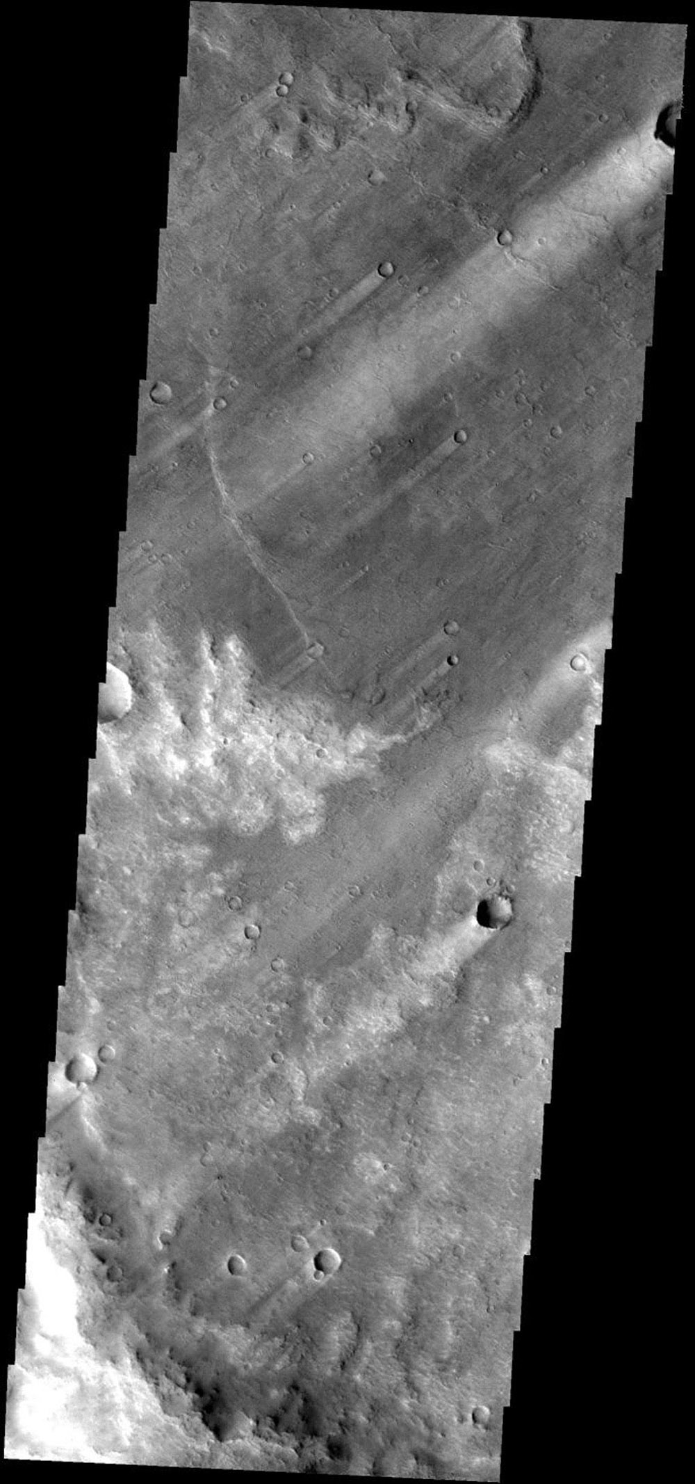 Windstreaks downwind of craters are a common feature in this region of Syrtis Planum on Mars as seen by NASA's Mars Odyssey spacecraft.