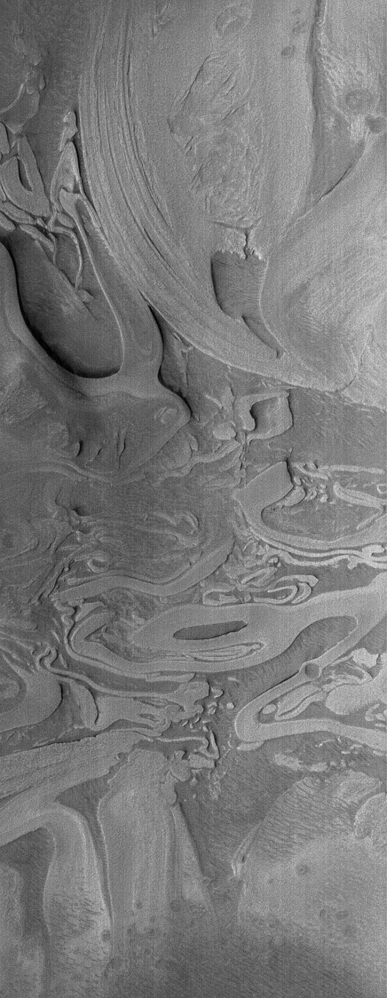 This image from NASA's Mars Global Surveyor shows an example of the extremely odd, seemingly scrambled layered rocks exposed by erosion near the deepest part of the deepest basin on Mars, Hellas.