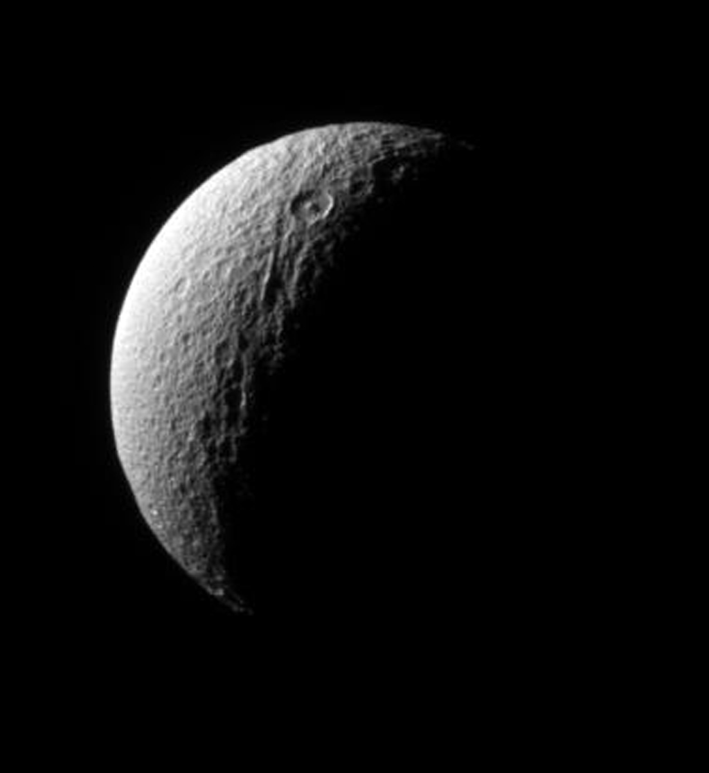 NASA's Cassini spacecraft surveys the ancient, craggy surface of Tethys, sighting the crater Telemachus with its prominent central peak.