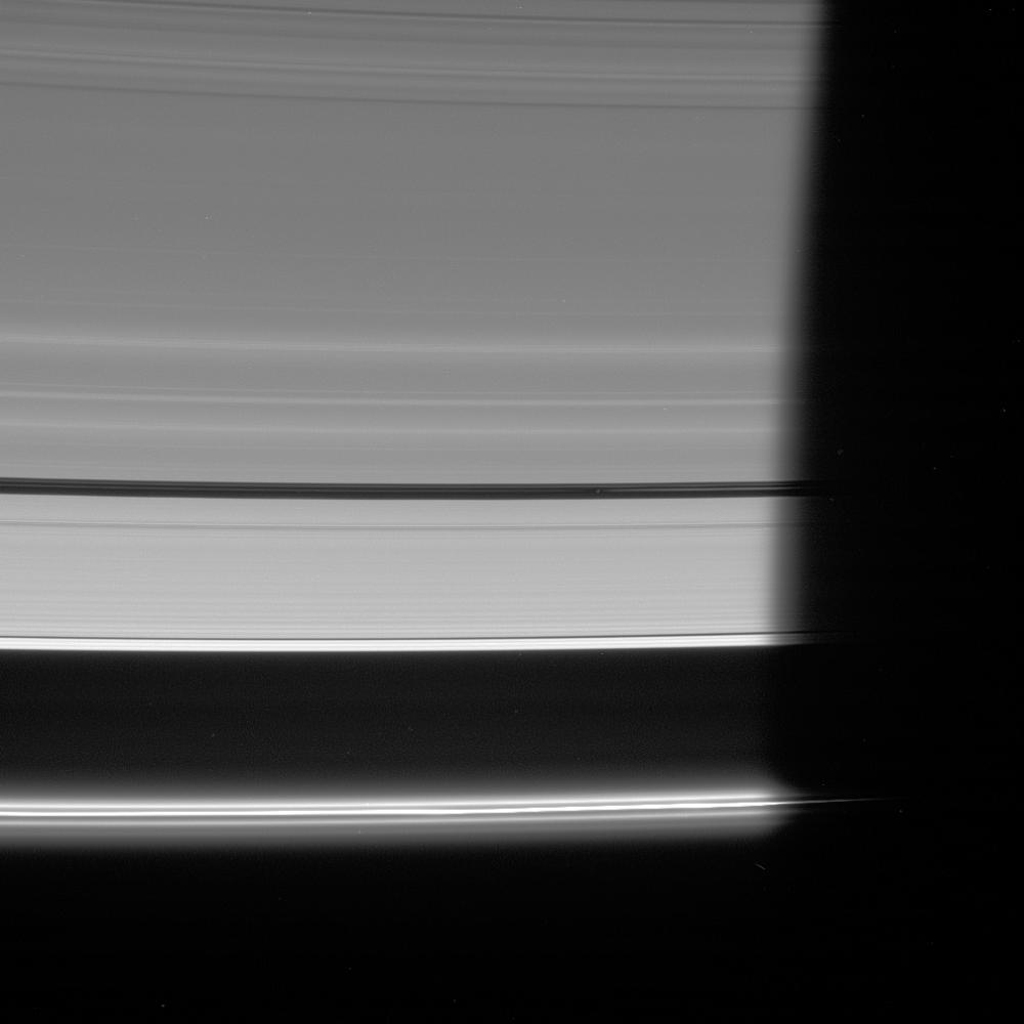 NASA's Cassini spacecraft looks down at the unlit side of the rings as Pan heads into Saturn's shadow. The moon is accompanied by faint ringlets in the Encke Gap.