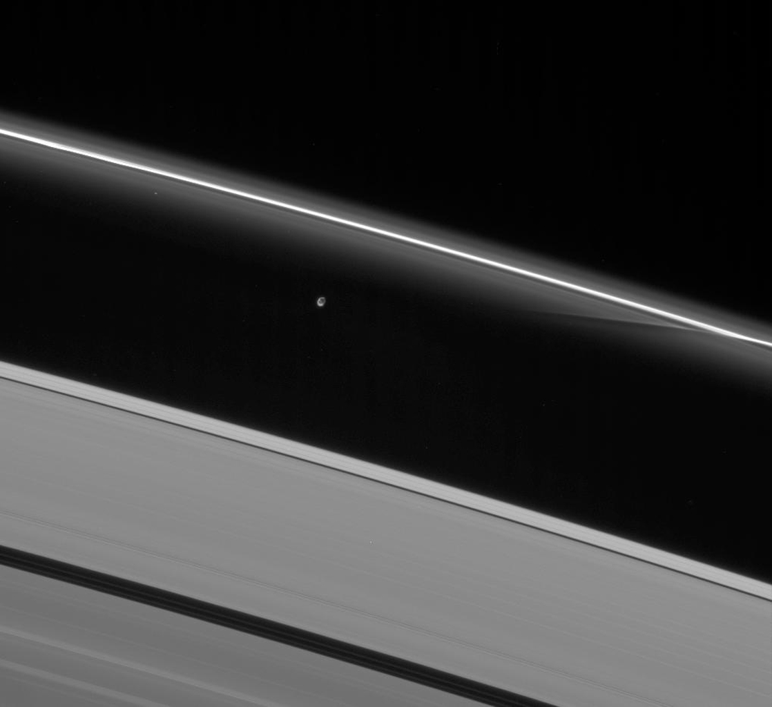Prometheus interacts gravitationally with the inner flanking ringlets of the F ring, creating dark channels as it passes. This image is from NASA's Cassini spacecraft.