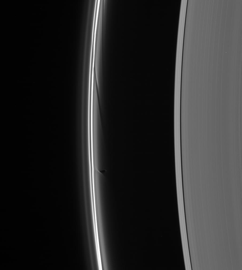 Prometheus dips into the inner F ring at its farthest point from Saturn in its orbit, creating a dark gore and a corresponding bright streamer as seen by NASA's Cassini spacecraft.