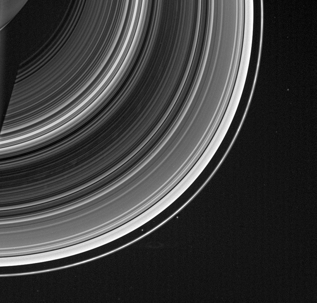 From on high, NASA's Cassini spacecraft spots a group of faint spokes against the striped landscape of the B ring, the dark region in the middle of the rings here. The spokes appear as irregular blotches.