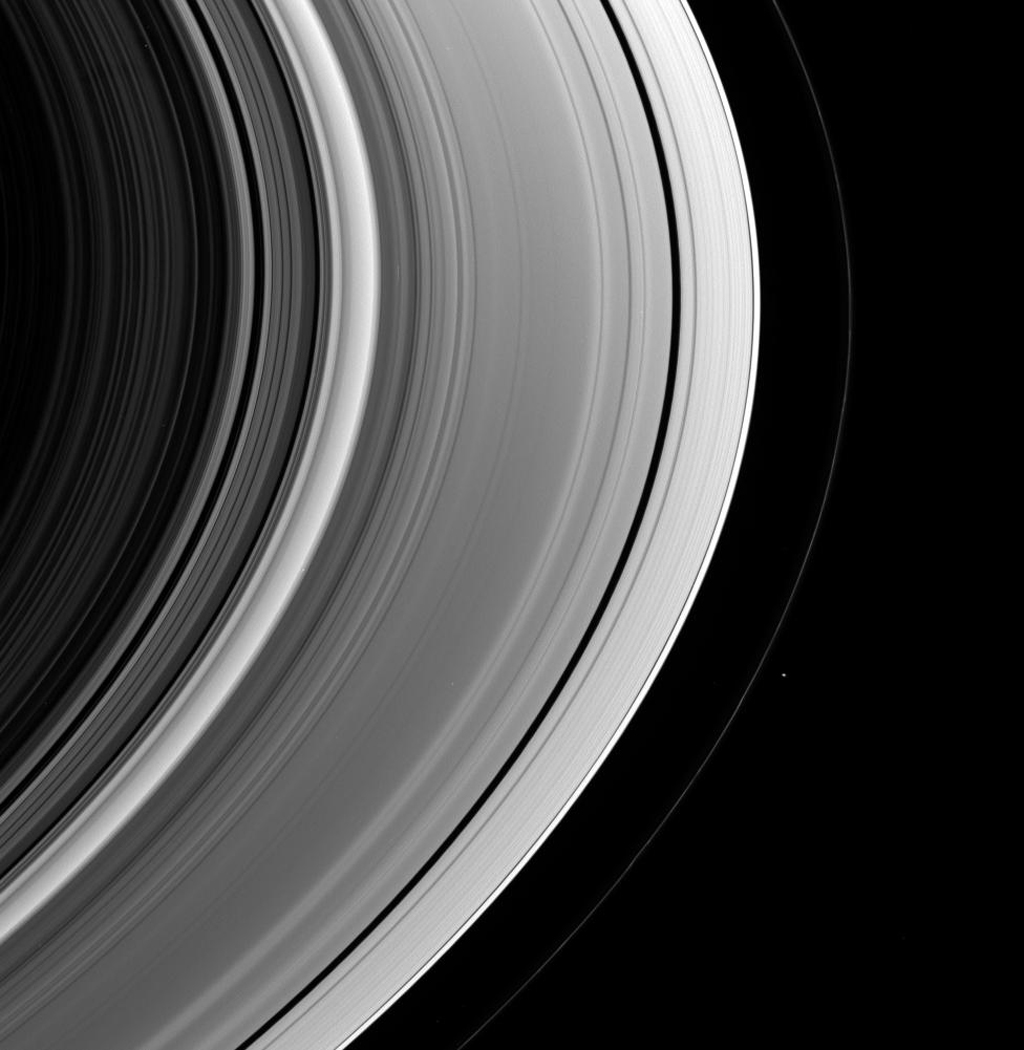 This view of the unlit side of Saturn's rings captures the small shepherd moon Pandora as it swings around the outside of the F ring. This image is from NASA's Cassini spacecraft.