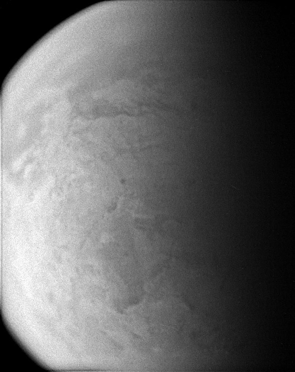 Straining to make out the surface of Titan through its murky atmosphere, NASA's Cassini spacecraft's wide angle camera manages to exploit one of the infrared spectral windows where the particulate smog is transparent enough for a peek.
