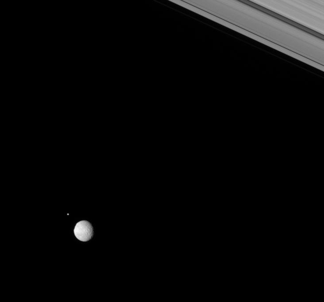 Two moons of Saturn, Pan and Pandora, rendezvous in the Saturnian skies above NASA's Cassini spacecraft.