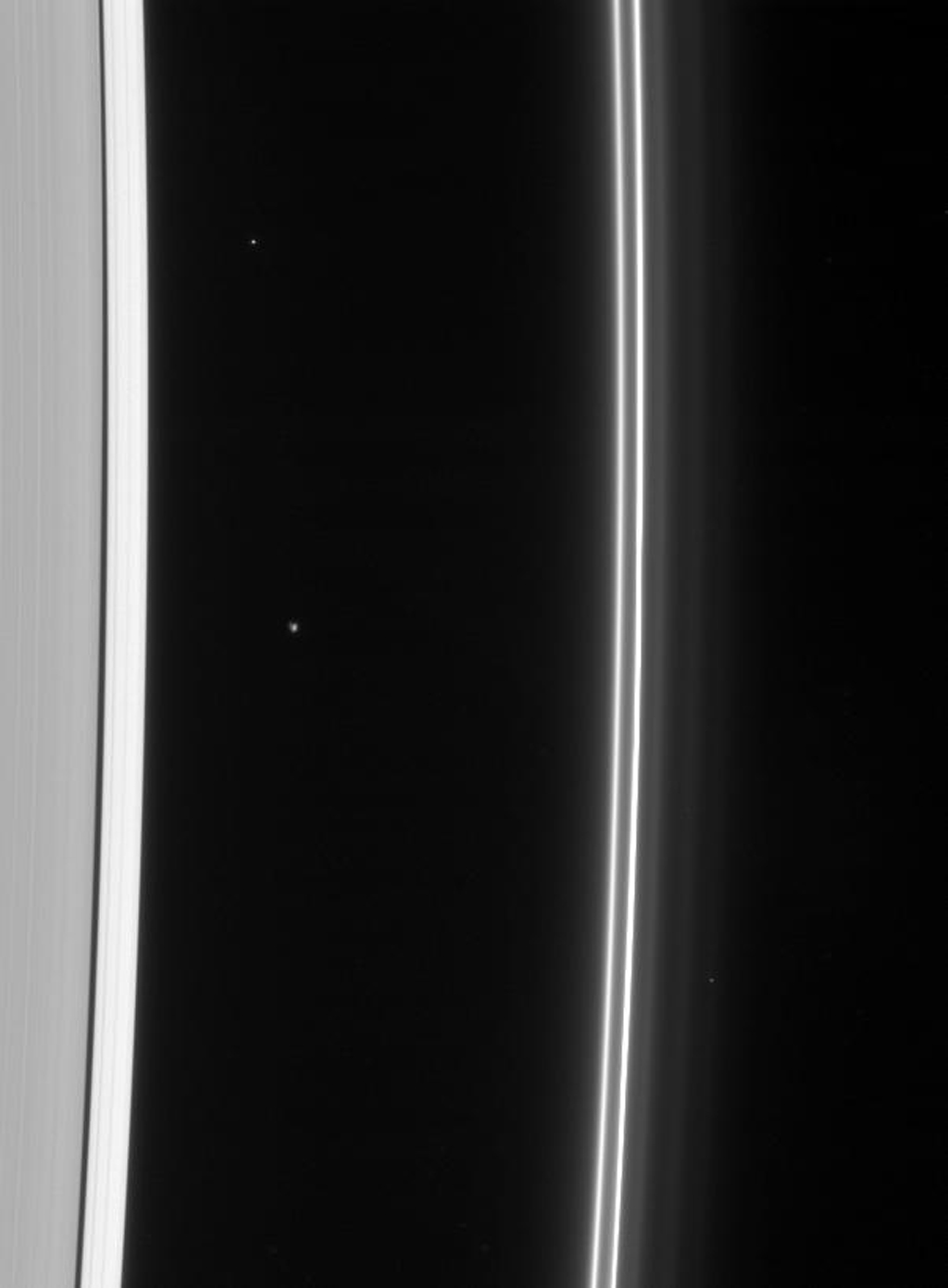 NASA's Cassini spacecraft gazes toward the multiple strands of the ever-changing F ring, also sighting Atlas at its station just beyond the A ring edge. A few faint background stars are visible in this image.