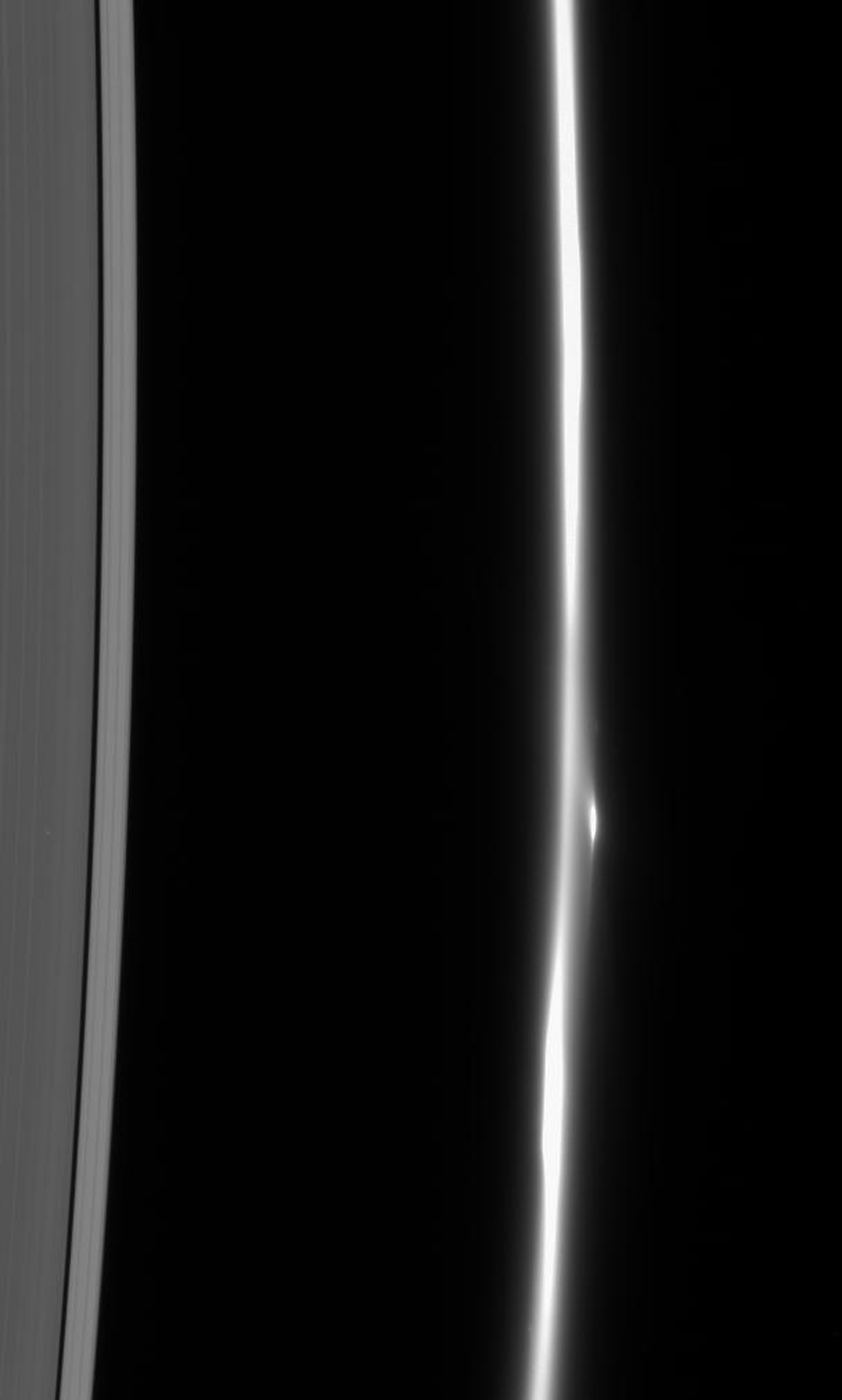 The F ring dissolves into a fuzzy stream of particles -- rather different from its usual appearance of a narrow, bright core flanked by dimmer ringlets. A bright clump of material flanks the ring's core as seen by NASA's Cassini spacecraft.