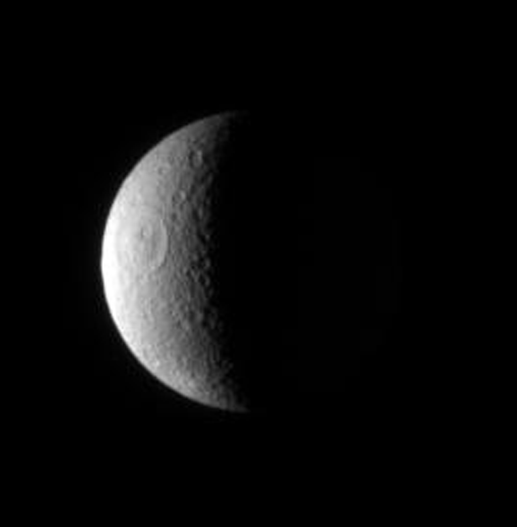 NASA's Cassini spacecraft examines the desolate, cratered crescent of Rhea, a surface so heavily bombarded over the eons that new craters are virtually guaranteed to form on top of older ones. The large Tirawa impact basin is visible here
