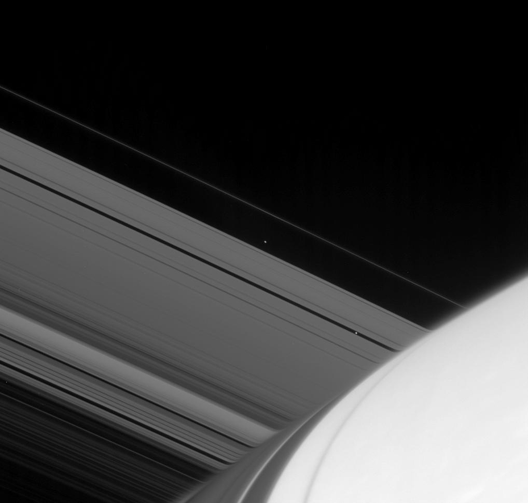 Atlas and Pan emerge from the far side of Saturn in this image captured by NASA's Cassini spacecraft. Light passing through the upper reaches of the planet's atmosphere is refracted, or bent, distorting the image of the rings beyond.