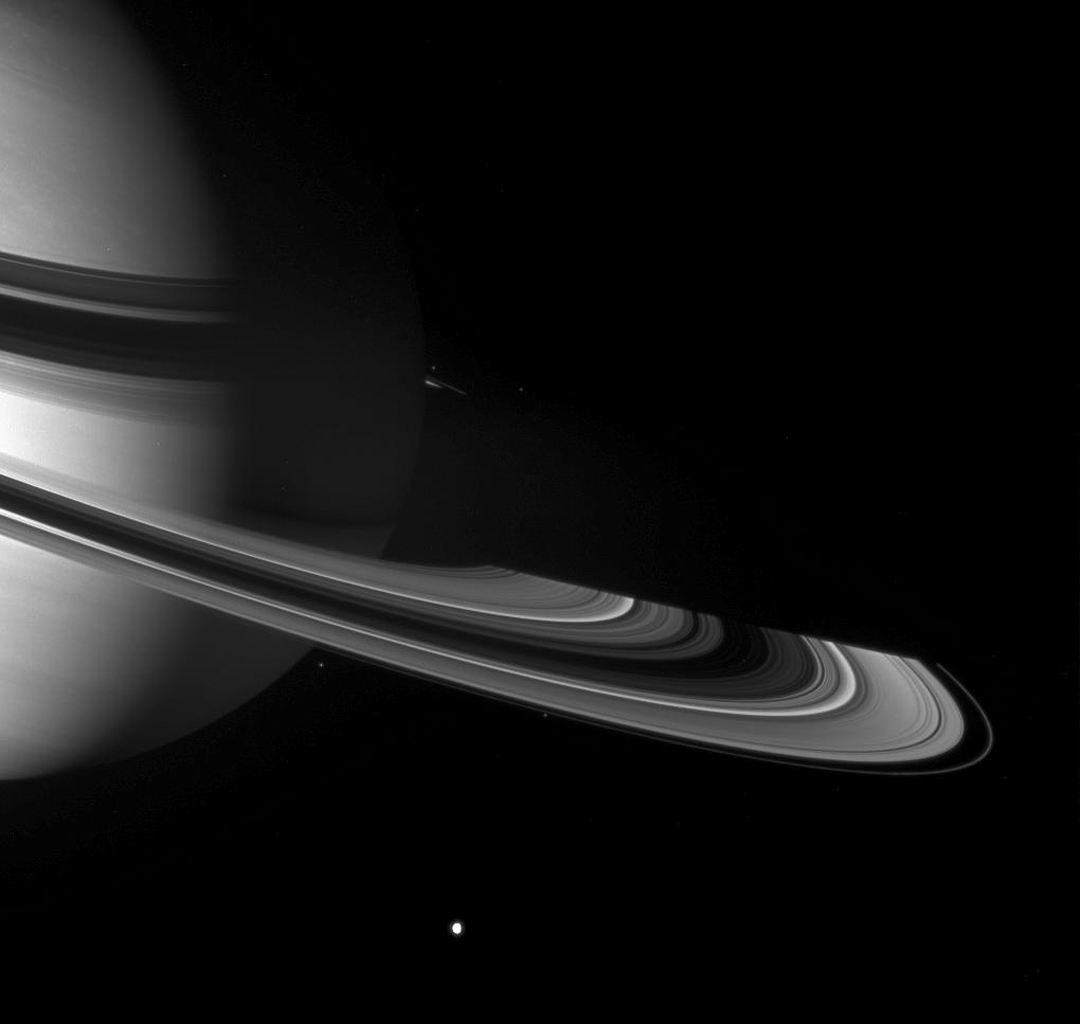Graceful giant Saturn poses with a few of the small worlds it holds close. From this viewpoint NASA's Cassini spacecraft can see across the entirety of the planet's shadow on the rings, to where the ringplane emerges once again into sunlight.