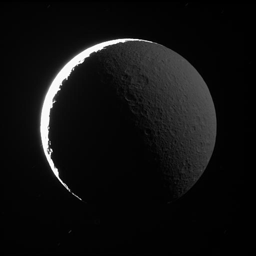 The night side of Rhea shines softly in reflected light from Saturn, as captured in this image from NASA's Cassini spacecraft. A similar effect, called Earthshine, can often be seen dimly illuminating the dark side Earth's moon.