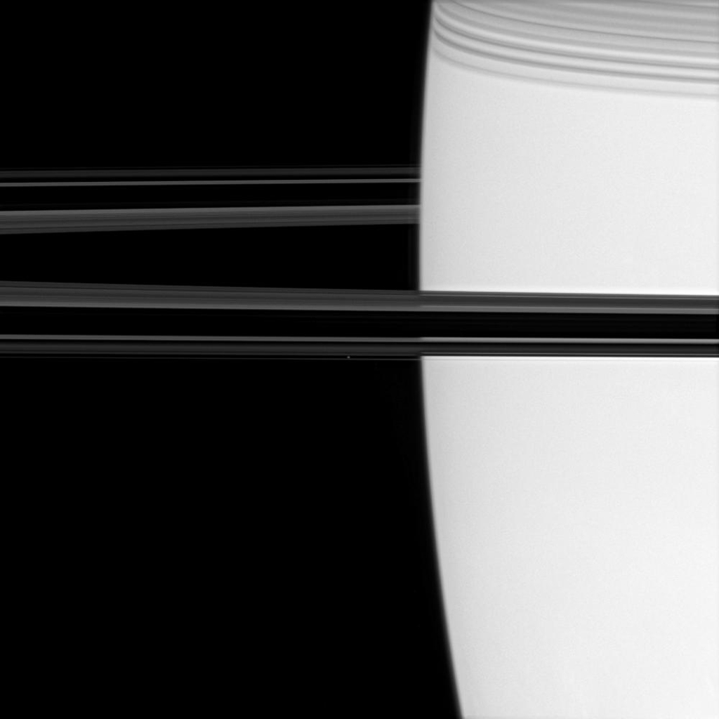 Off the shoulder of giant Saturn, a bright pinpoint marks the location of the ring moon Atlas (image center). Shadows cast by the C ring adorn the planet at upper right as seen by NASA's Cassini spacecraft.