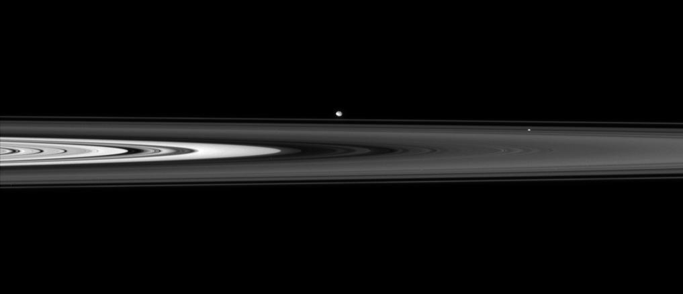 NASA's Cassini spacecraft skims past Saturn's ringplane at a low angle, spotting two ring moons on the far side.