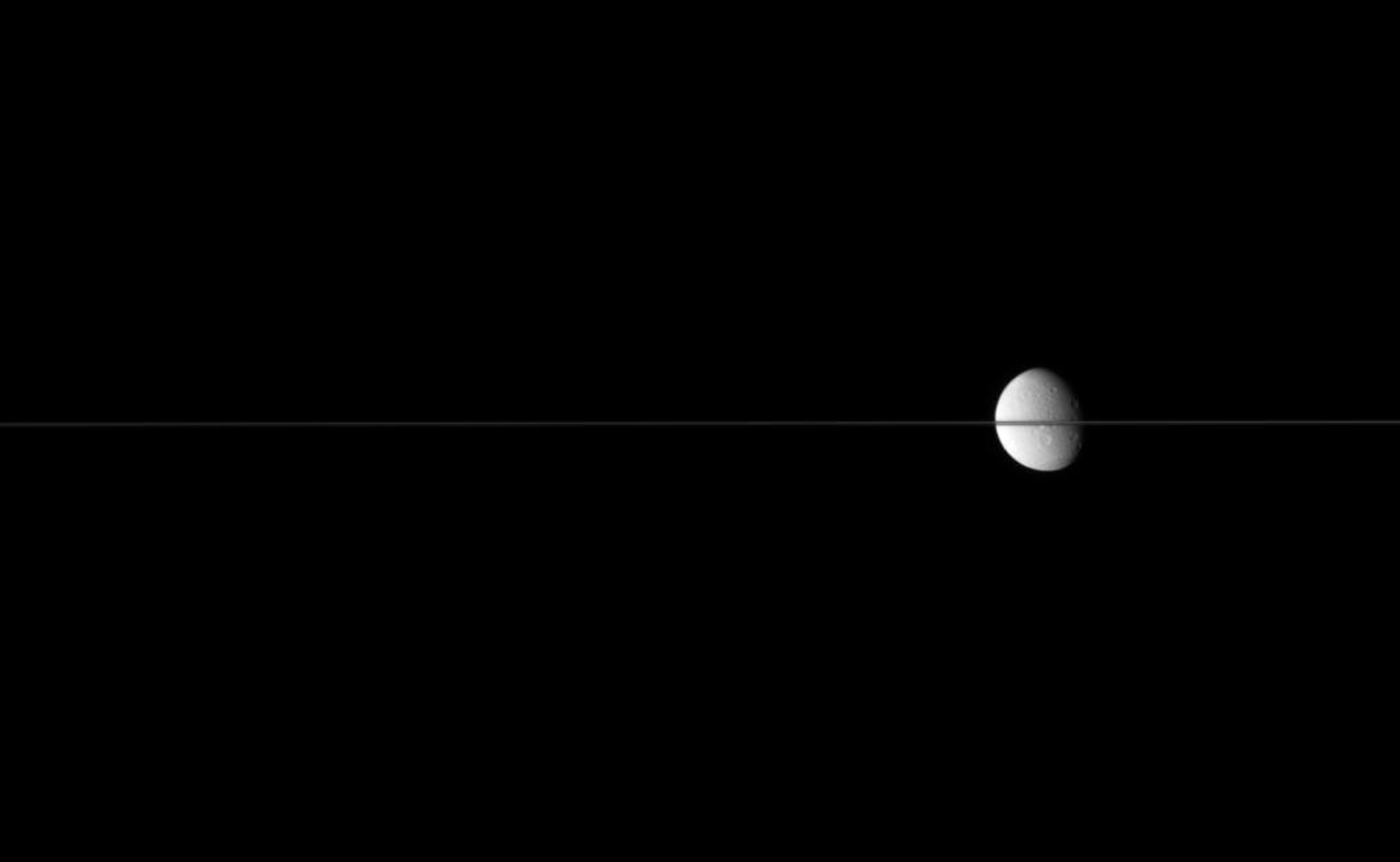 Dione floats in the sea of space, bisected by Saturn's edge-on ringplane. This image was taken in visible light with NASA's Cassini spacecraft's narrow-angle camera on July 2, 2007 at a distance of approximately 2.5 million kilometers from Dione.