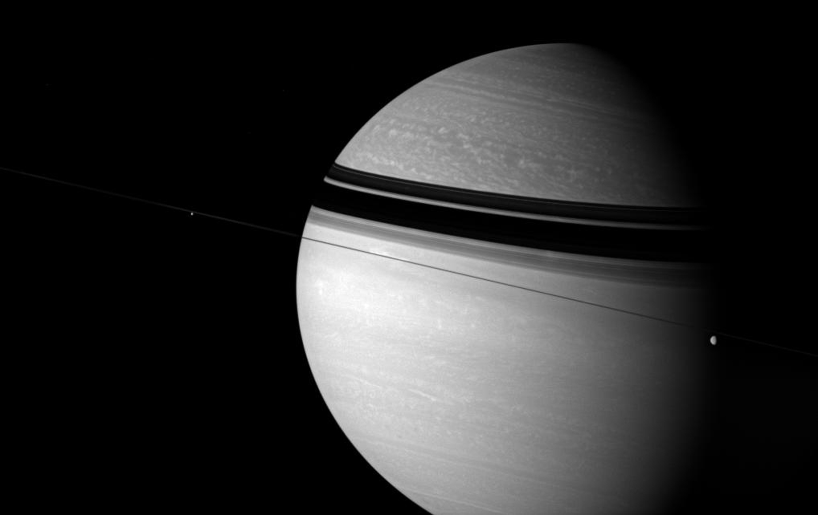 Rhea and Enceladus float across the field of view as bright clouds roll through the gas giant Saturn's skies in this image from NASA's Cassini spacecraft.
