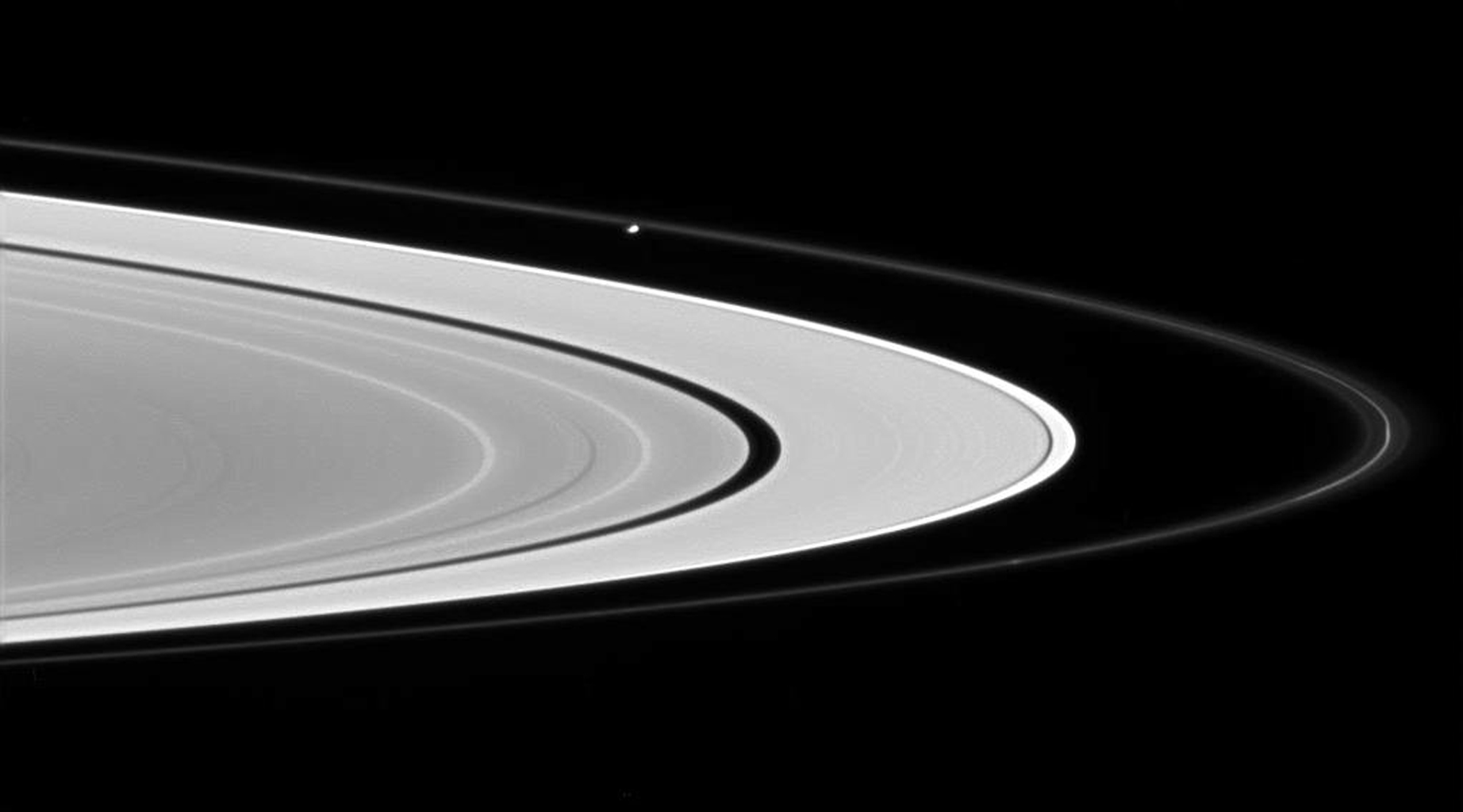 Prometheus glides across the scene from left to right, sculpting and perturbing particles in Saturn's F ring. This image was taken in visible light with NASA's Cassini spacecraft's wide-angle camera on June 28, 2007.