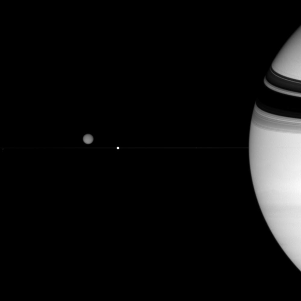 Three of Saturn's diverse family of moons are captured in this view from NASA's Cassini spacecraft. Titan hovers above the thin line of the rings. Epimetheus is a mere speck at far left. Enceladus sits in front of the ringplane from Cassini's view.
