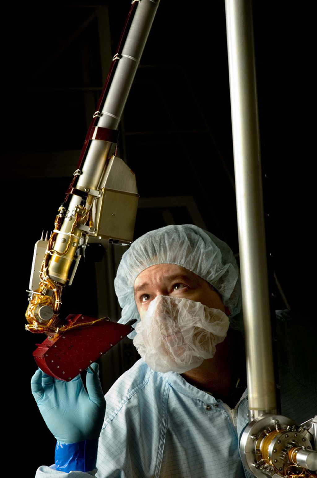 A spacecraft technician inspected the vital robotic arm of NASA's Phoenix Mars Lander during the assembly phase of the mission