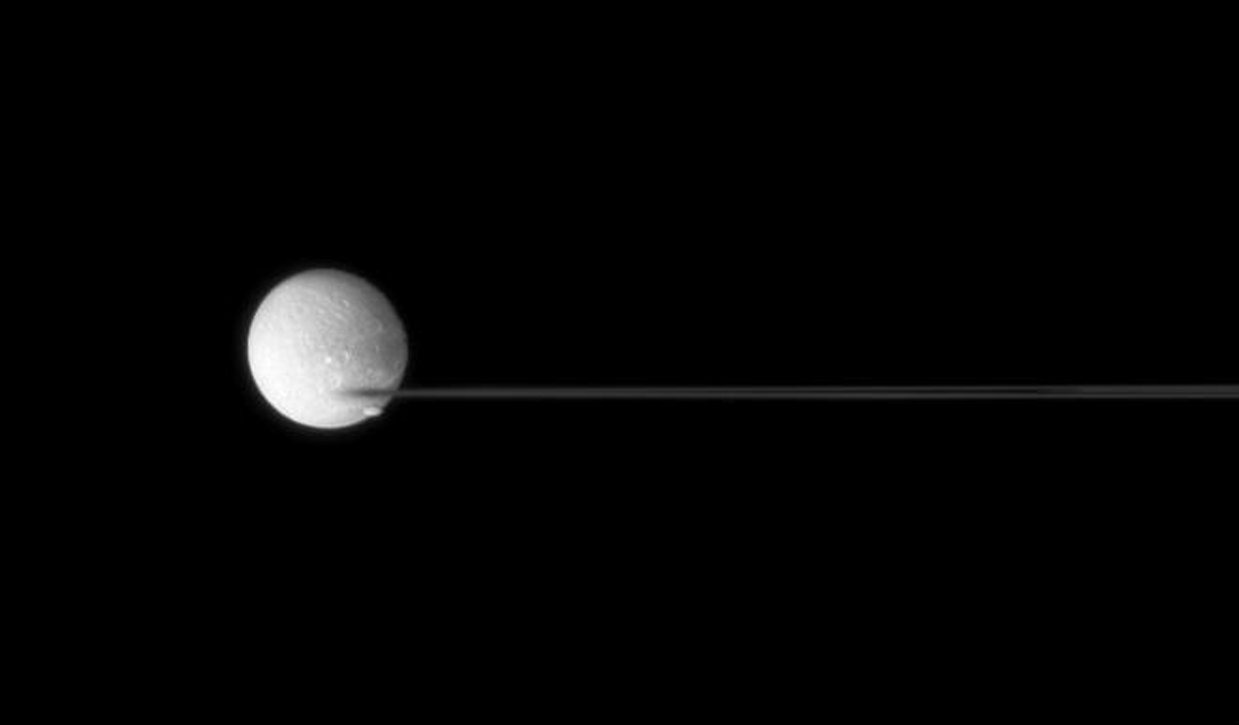 Saturn's nearly edge-on rings are caught between two moons, Dione and Pandora taken by NASA's Cassini spacecraft.