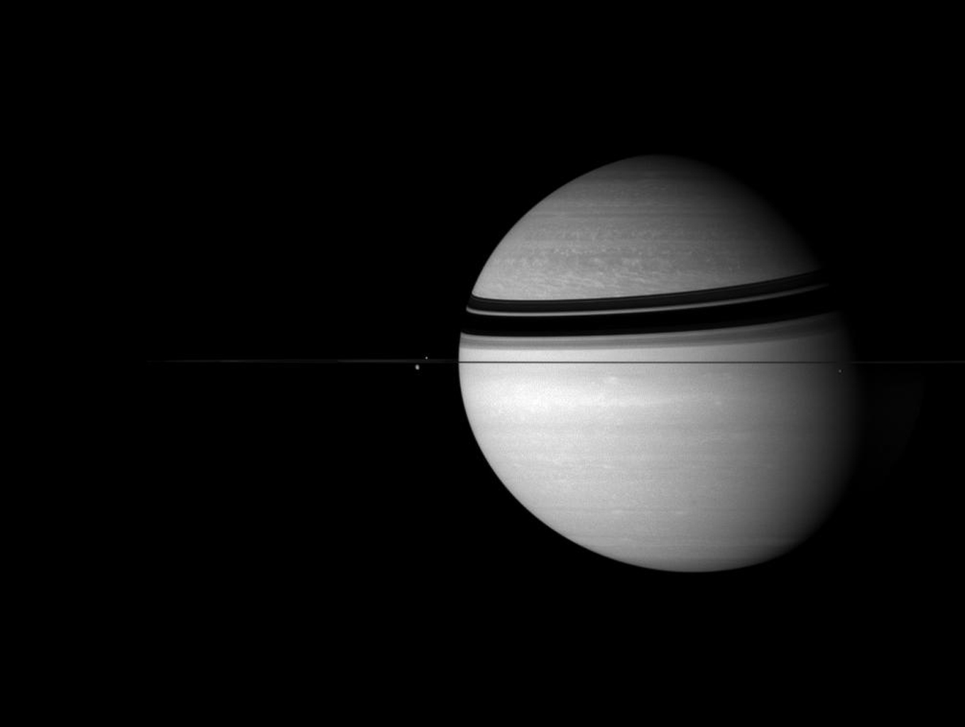 Saturn sits with its attendants in the icy depths of the outer Solar System in this image from NASA's Cassini spacecraft.