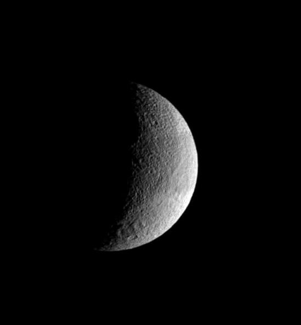 The pockmarked crescent of Tethys displays slightly darker terrain in a band at its equator. The rim of the great crater Odysseus lurks on the terminator. This image was taken in visible light with NASA's Cassini spacecraft's wide-angle camera.