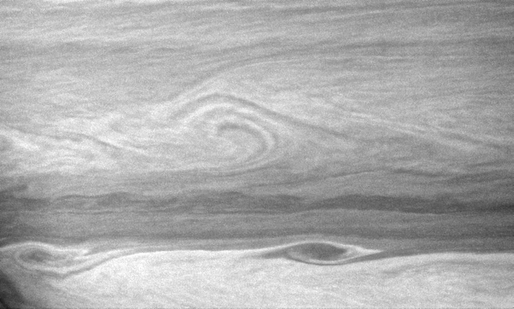 Large vortices edge their way along the turbulent boundary between east-west flowing cloud bands. This view captured by NASA's Cassini spacecraft is centered on a region 22 degrees south of Saturn's equator.