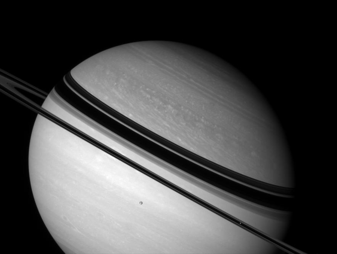 Shadow-draped Saturn rests on its side as two icy moons glide past in this image from NASA's Cassini spacecraft. Dione hangs against the planet's bright southern hemisphere. Mimas is a bright speck against the unlit side of the rings, near lower right.
