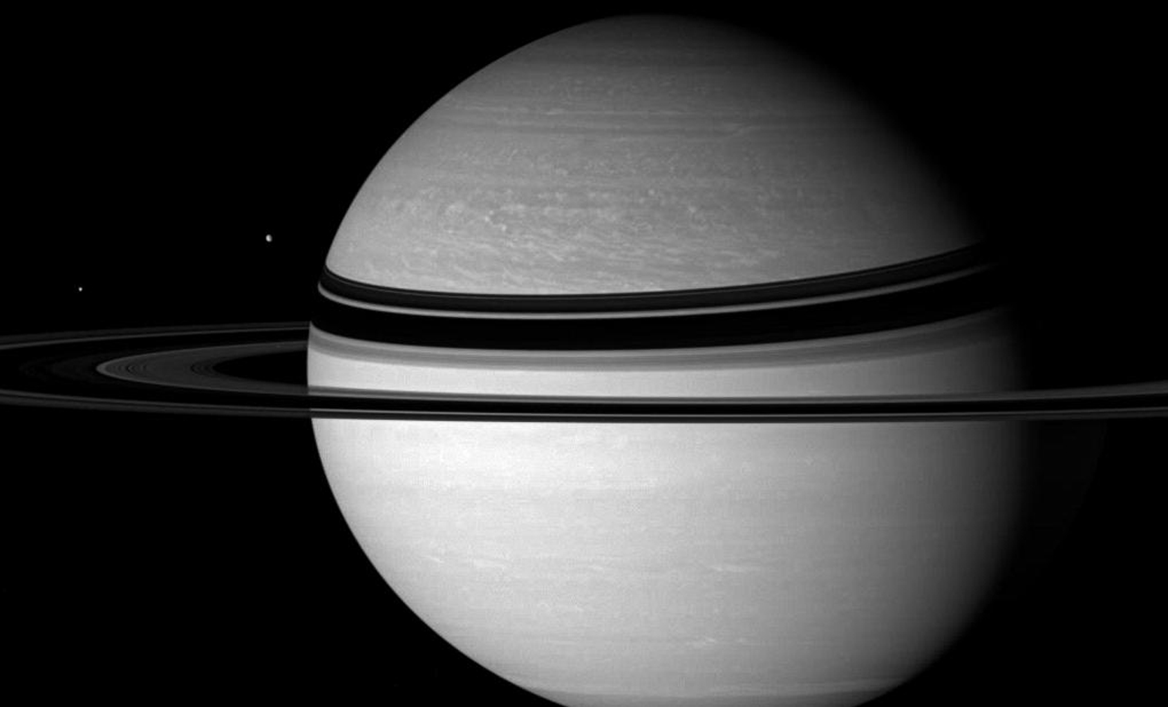 Saturn and Dione regard Enceladus, the object their gravitational tug-of-war in this image taken by NASA's Cassini spacecraft on Nov. 8, 2007.