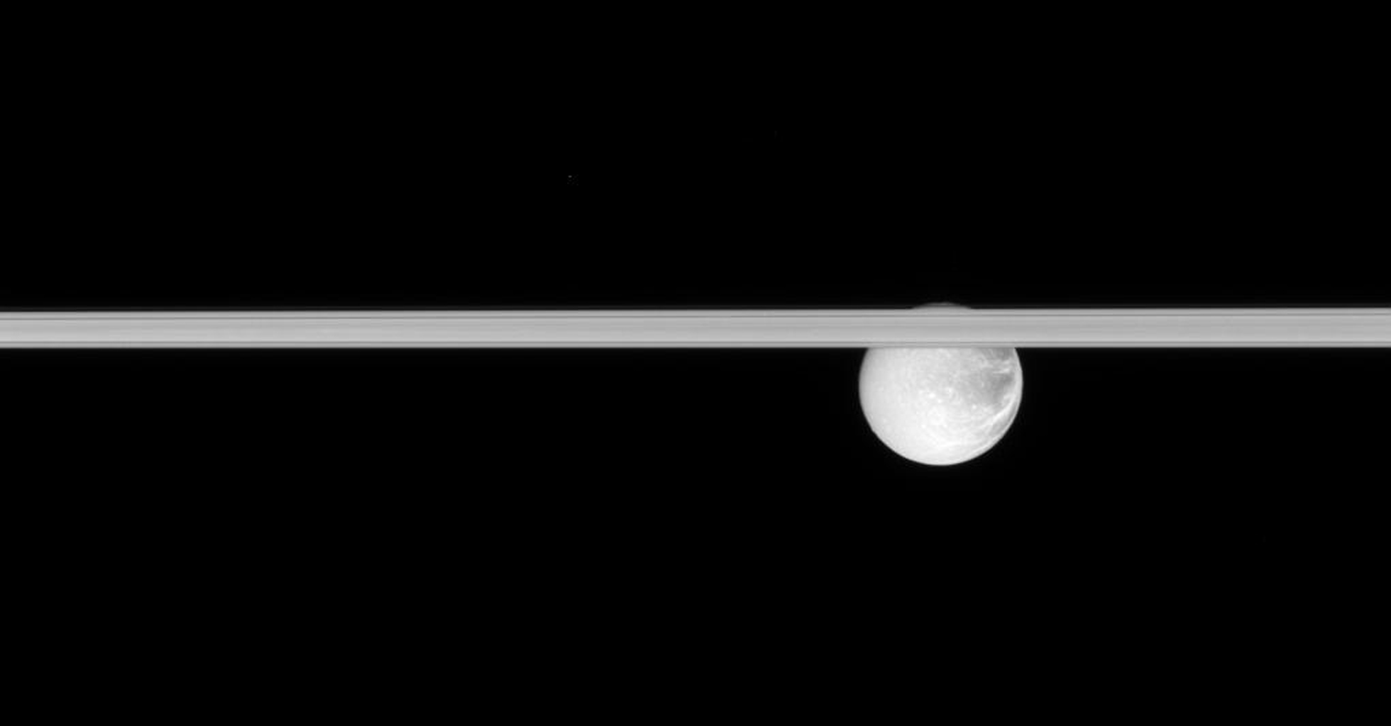 Saturn's rings slice across this scene, obscuring the cracked face of Dione. This image was taken in visible light with NASA's Cassini spacecraft's narrow-angle camera on Jan. 17, 2008.