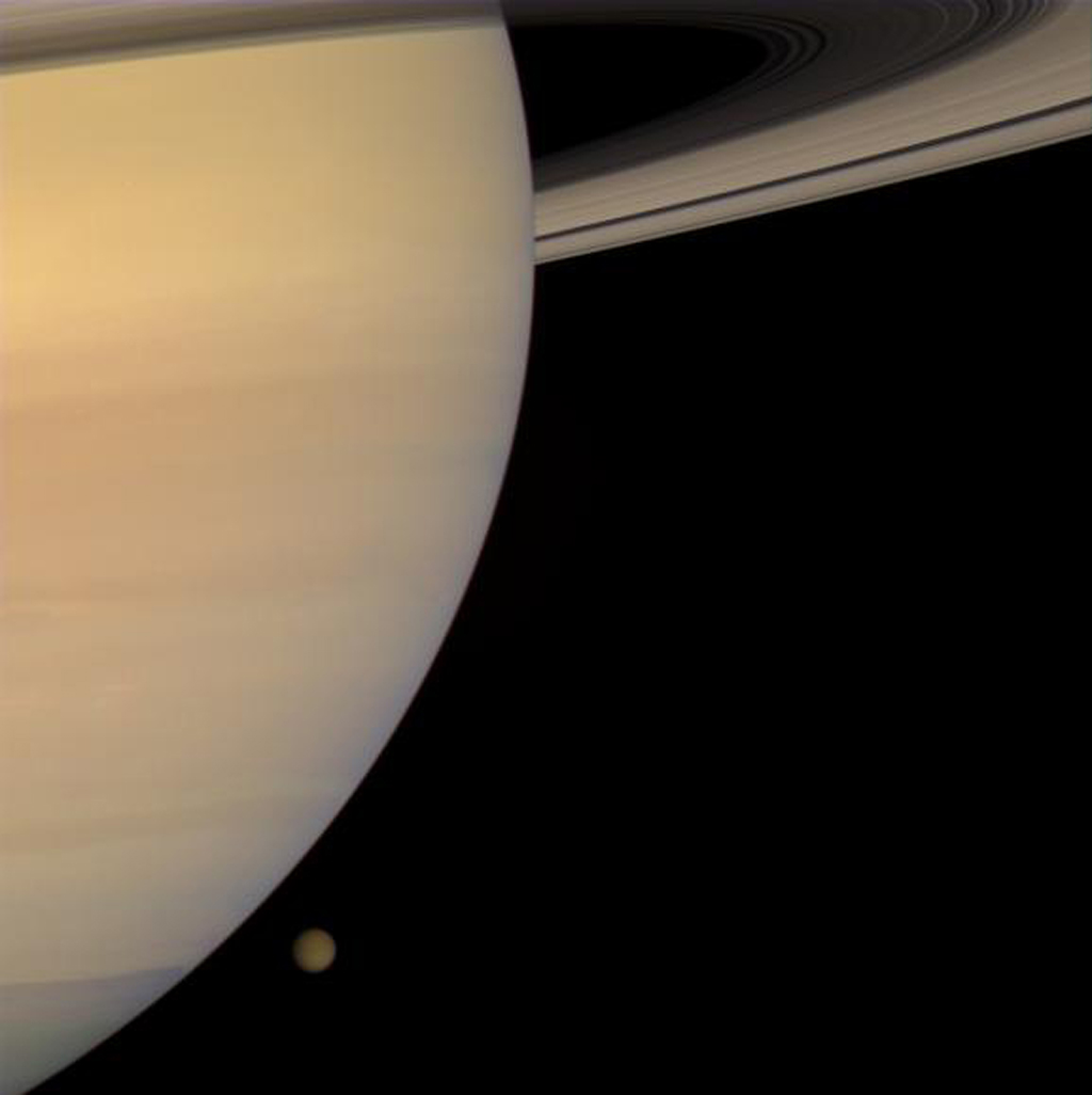 NASA's Cassini spacecraft captured this color portrait of Saturn and Titan only a few minutes before the haze-enshrouded moon slipped behind the planet's enormous bulk.