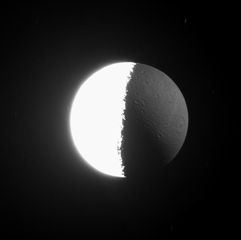 As Cassini images often show, the Sun is not the only source of illumination in the Saturn System. The huge, reflective planet also shines upon its moons. This image from NASA's Cassini spacecraft looks almost directly down onto the north pole of Dione.