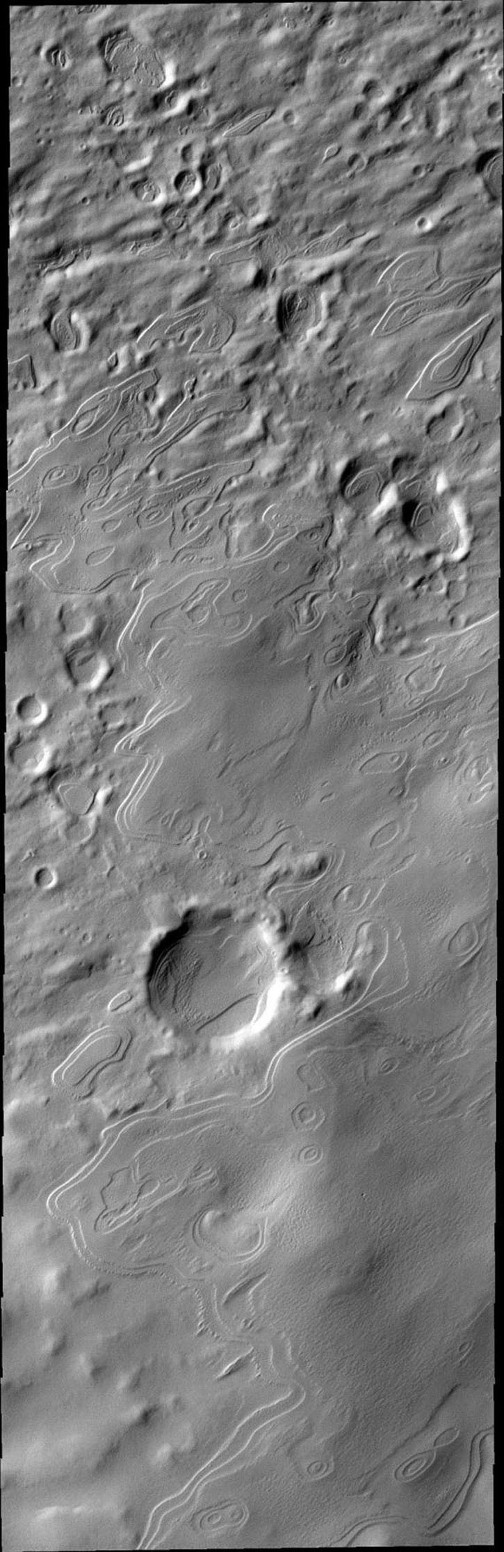 This image from NASA's Mars Odyssey spacecraft shows layered mounds are south polar layered deposits that are no longer part of Mars' south polar cap. Their location marks a time when the permanent polar cap was more extensive.